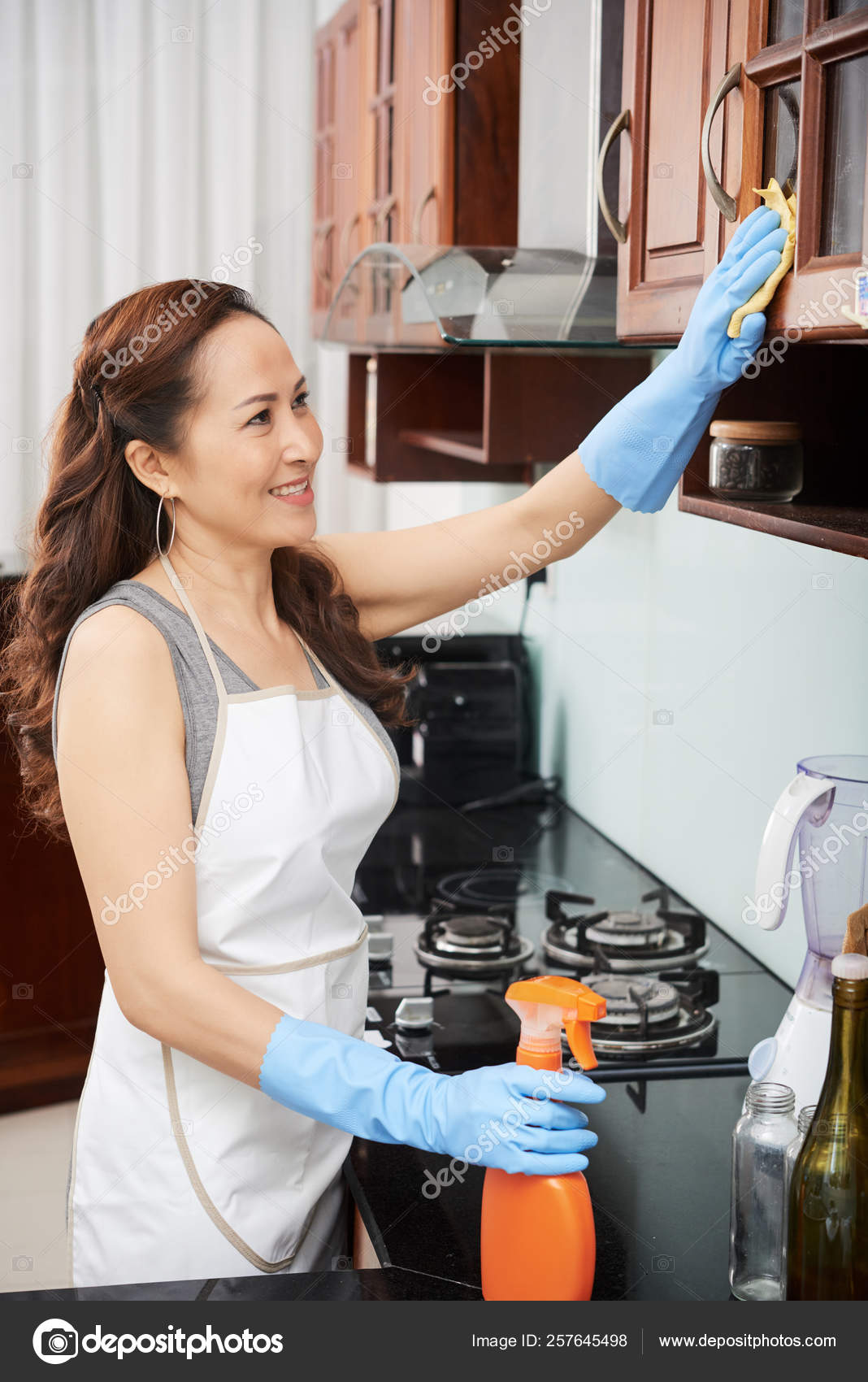 Smiling Mature Asian Woman Cleaning Cupboards Kitchen Stock