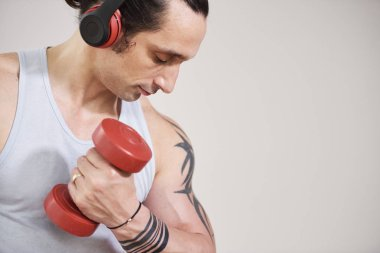 Handsome fit young man listening to music in headphones when pumping biceps