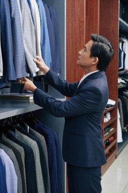 Mature Vietnamese businessman choosing suit in boutique