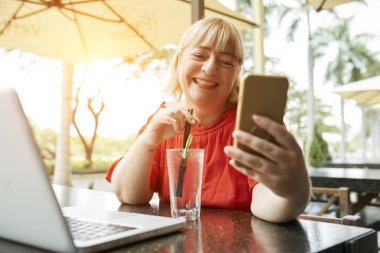 Cheerful woman enjoying glass of refreshing lemonade in outdoor cafe and videocalling with mobile phone