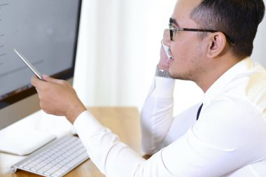 Asian business executive discussing information on computer with colleague on phone