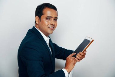 Portrait of Indian professional in suit working online on digital tablet and smiling at camera over white background