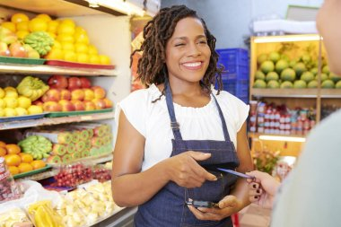 Smiling pretty young grocery store worker with card reader talking to customer