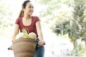 Šťastná mladá vietnamská žena jezdila domů z místního trhu s košíkem plným čerstvé zeleniny