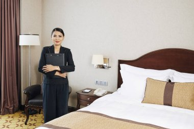 Portrait of Asian young manager in formalwear and with folder in her hands standing in the hotel room and looking at camera stock vector