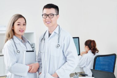Portrait of smiling young Vietnamese general practitioners in white labcoats, their colleague working on computer in background