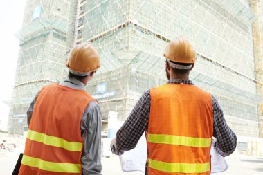 Rear view of two construction workers in hardhats and reflective vests holding blueprint and looking together at high building under construction outdoors stock vector