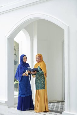 Smiling pretty muslim women in traditional dresses reading holy quaran together