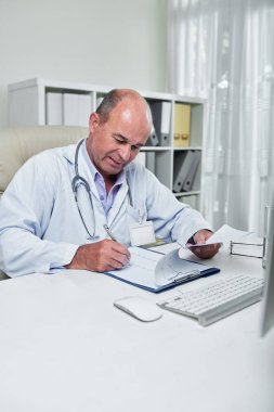 Serious experienced cardiologist sitting at table in his office and checking cardiogram of patient