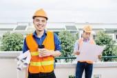 Lächelnder Bauingenieur, der mit vielen Bauplänen im Freien steht und Kaffee zum Mitnehmen trinkt, sein Mitarbeiter mit Bauplan im Hintergrund