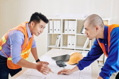 Head engineer and contractor having meeting in office and discussing construction plan and upcoming work stock vector