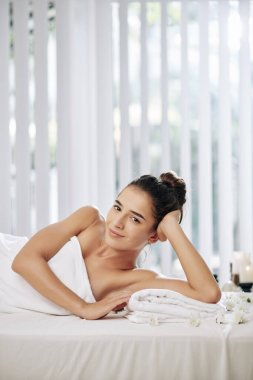 Attractive smiling young woman in white fluffy towel lying on massage bed in spa salon