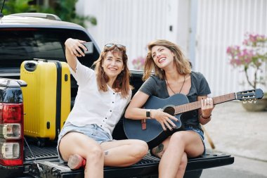 Pretty positive young woman taking selfie with her friend playing guitar when sitting in car trunk
