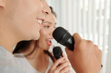 Close-up image of smiling young people singing in microphones at home