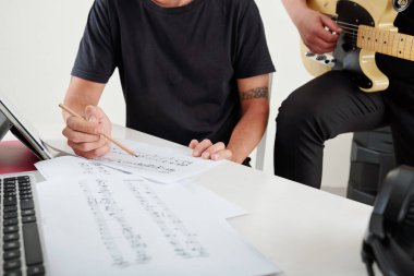 Composers playing guitar and writing musical notes on paper sheets when working on new song for band