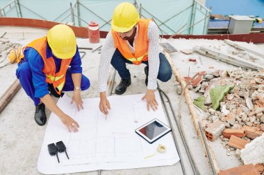 Engineers in hardhats discussing details of house blueprint when working at construction site stock vector