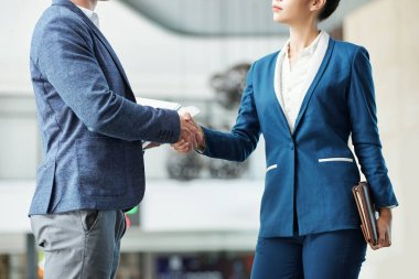 Cropped image of serious young male and female entrepreneurs shaking hands
