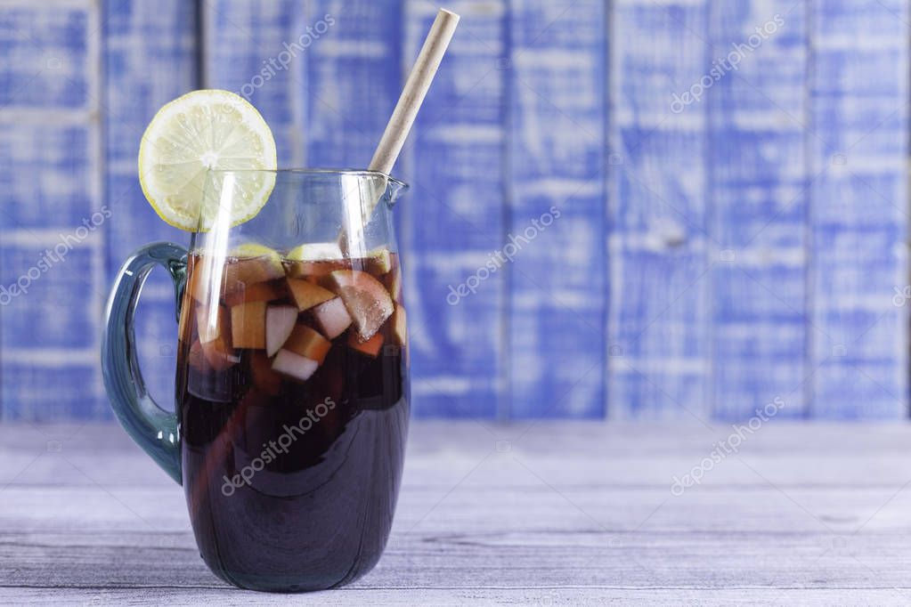 spanish sangaree  jug with raw fruits and lemon slice on wood table and blue wood background