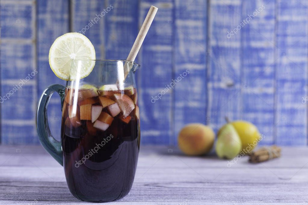 spanish sangaree  jug with raw fruits, cinnamon sticks and lemon slice on wood table and blue wood background
