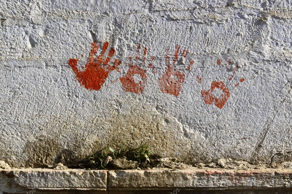 Red handprints on the dirty wall on the street, Pushkar, Rajasthan, India
