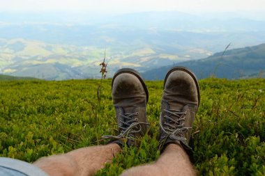 Traveler legs boots in green grass against mountains valley view. Man is resting during hiking. Travel lifestyle adventure vacations concept. Carpathians, Ukraine.