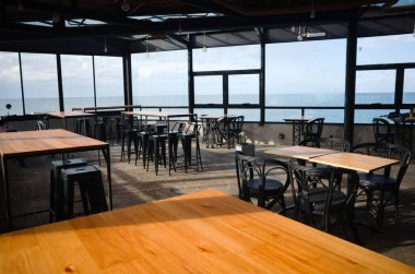 Interior view of closed empty cafe. Chairs and tables of empty restaurant on the beach with ocean view during quarantine in 2020. Mar del Plata, Argentina