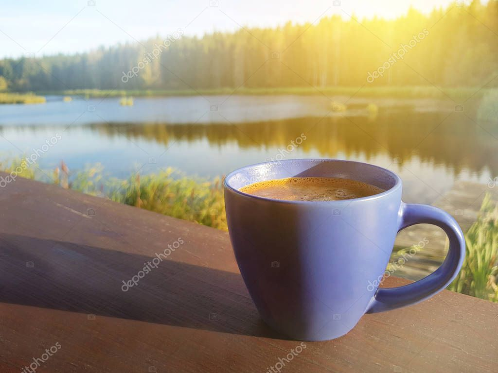 Cup of fresh aromatic coffee by a lake in the morning