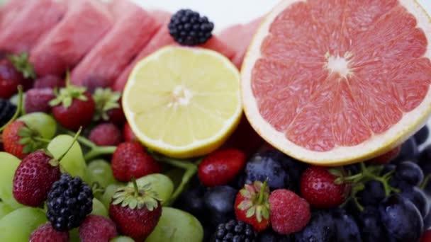 Krásné smíšené bobule a ovoce na bílém pozadí. Zdravé jídlo zblízka. 4k
