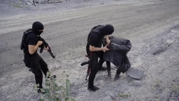 Dva bezpečnostní stráže se zbraněmi drží zadržení pachatele na místě činu