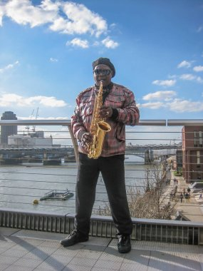 London / England / UK - 02/19/2013: View at the male musician playing sax on bridge, banks of the River Thames in central London on background