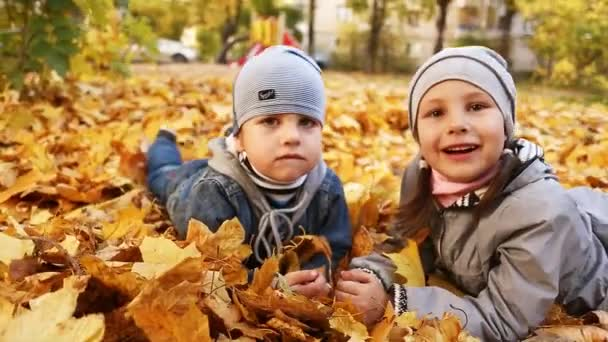 Happy boy and girl play in autumn foliage