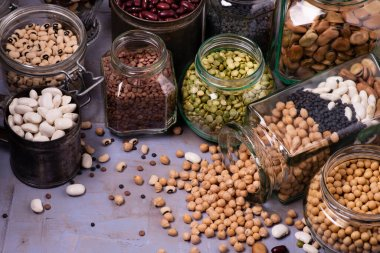 large variety of dried legumes in glass jars. background texture with top view