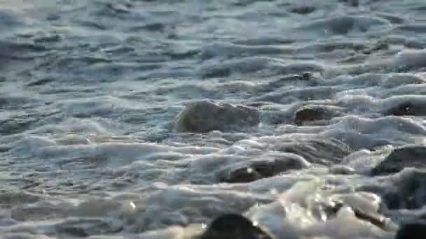 Moře-vlny koupání oblázky a kameny na pobřeží při západu slunce