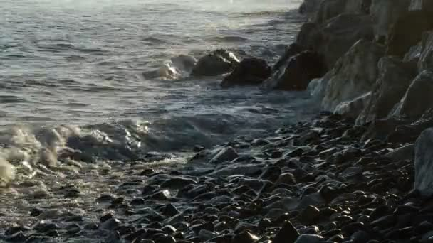 Shore with sea waves breaking at the rocks and stones and pebbles in the shore