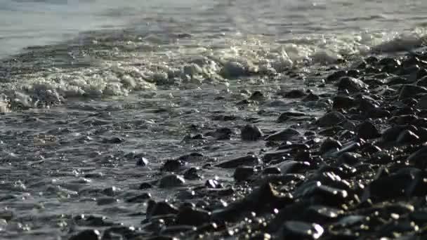 Západ slunce na pláži s výhledem na moře-vlny koupání oblázky a kameny