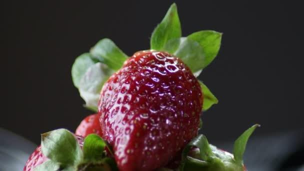 Jahodové ovoce kroužící v horách jahod v černém pozadí