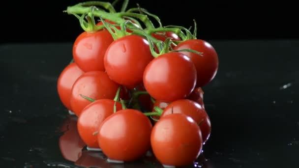 natürliche frische Kirschen Tomaten Kreiseln auf schwarzem Hintergrund