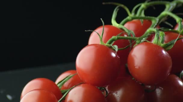 natürliche frische Tomaten Kirschen Kreiseln auf schwarzem Hintergrund