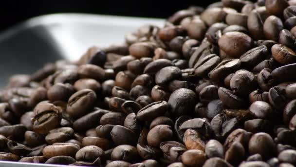 Kávová zrna kroužící na černém podnosu
