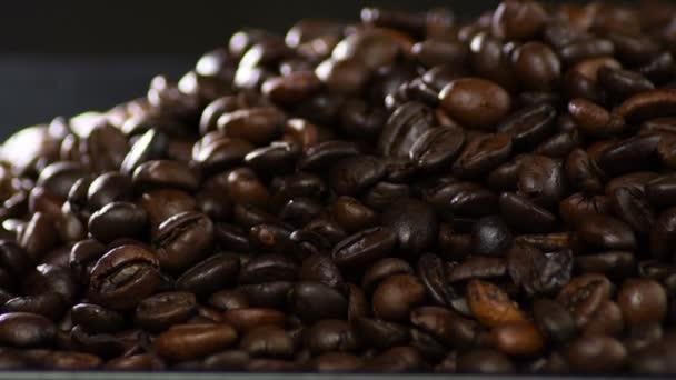 Hnědá pražená kávová zrna kroužící v černém podnosu