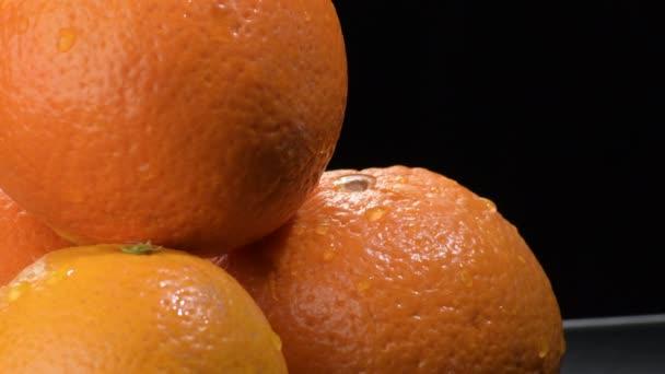 Fresh oranges fruit gyrating on black background