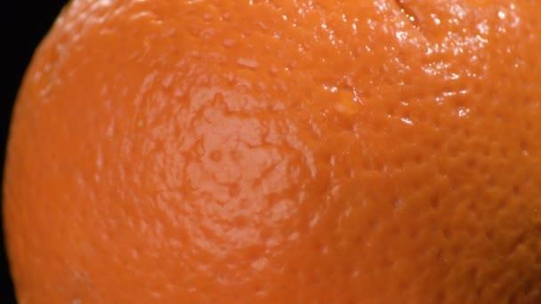 Orange skin fruit gyrating on black background