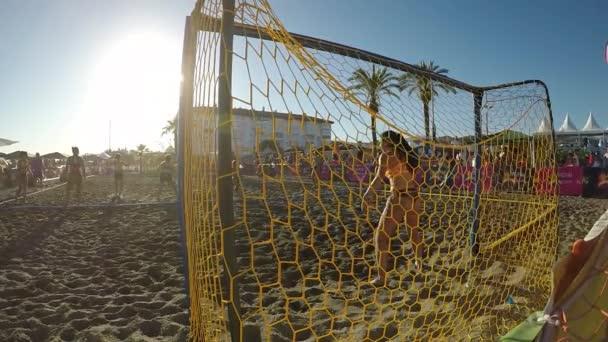 Goal in a play of match of beach handball of women at sunset