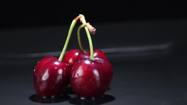 Three cherries gyrating on black background