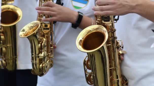 Különböző szaxofonokat játszó zenészek egy utcai zenekarban