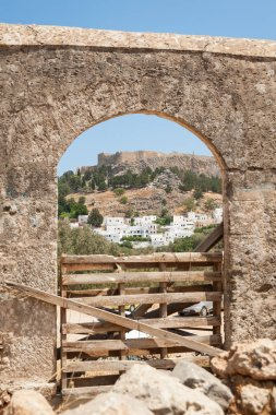 Distant view through stone arch opening at Lindos Town and Castle with ancient ruins of the Acropolis on sunny warm day. Island of Rhodes, Greece. Europe.