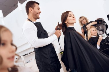 Hairdresser curling dark brown hair of beautiful woman. Woman care about hairstyle.