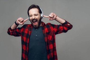Portrait of Guy Listening to Music with Headphones. Handsome Smiling Guy in Checkered Shirt with Closed Eyes with Amazed Expression. Isolated on Gray Background. Concept of People Emotions