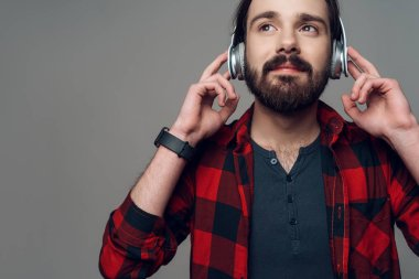 Joyful Man Listening to Music with Headphones. Cool Handsome Young Guy in Checkered Shirt with Calm Face Holds Earphones . Isolated on Gray Background. Concept of People Emotions