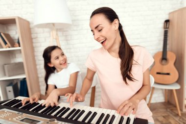 Mom and girl are playing the synthesizer at home. They rest and have fun.